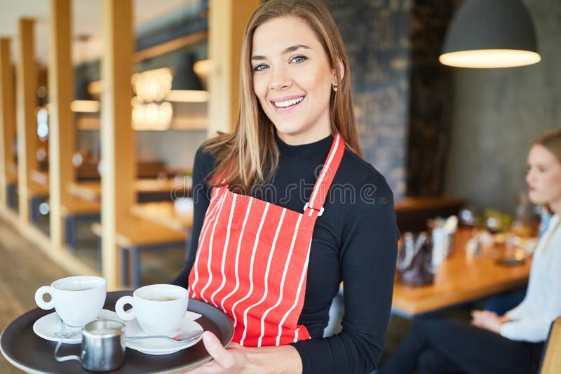 Friendly waitress with tray serving coffee royalty free stock image
