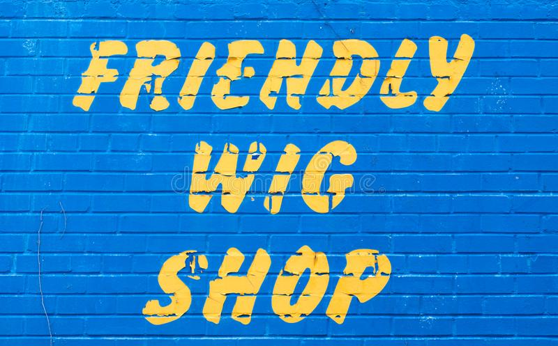 A friendly wig shop sign on a wall royalty free stock images