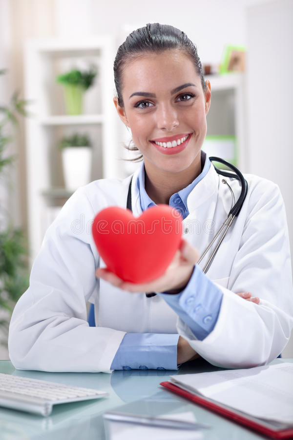 Friendly young female doctor holding a heart in his hands. Healthcare and medicine concept - smiling female doctor with heart and stethoscope stock photography