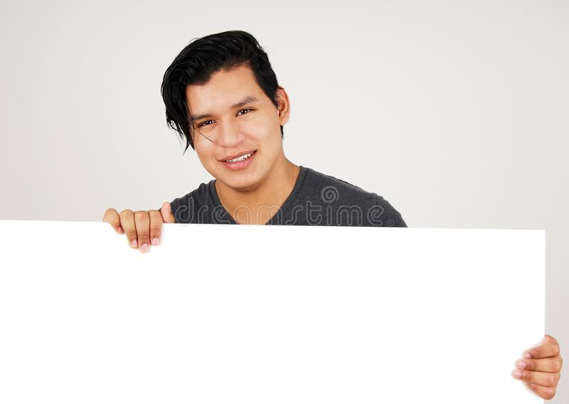Friendly young latino man holding white sign royalty free stock photography