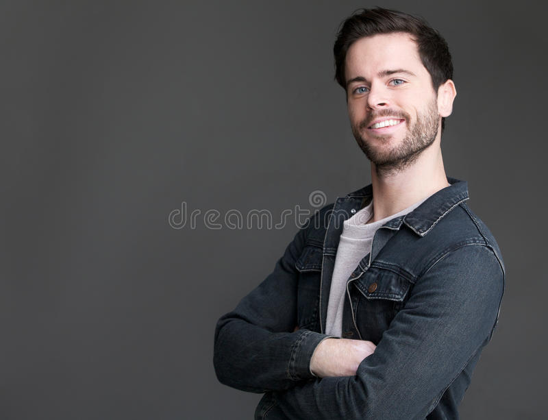 Friendly young man smiling with arms crossed stock photos