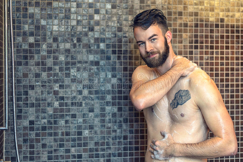 Friendly young man soaping himself in the shower stock photography