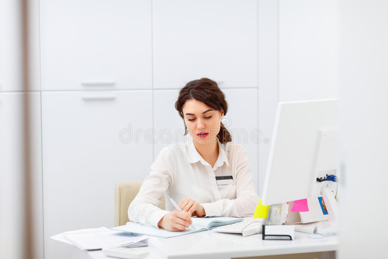 Friendly young woman behind reception desk administrator. Friendly young woman behind the reception desk administrator stock image