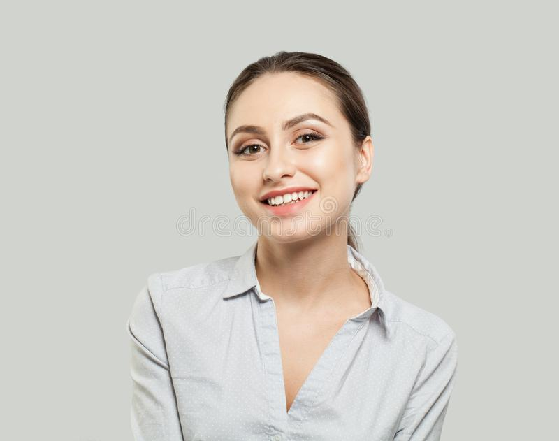 Friendly young woman smiling on white background royalty free stock photography