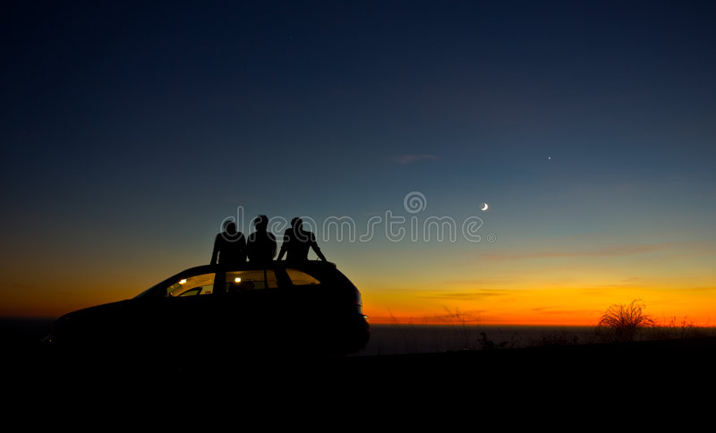 Friends. Three people sitting on a car watching sunset