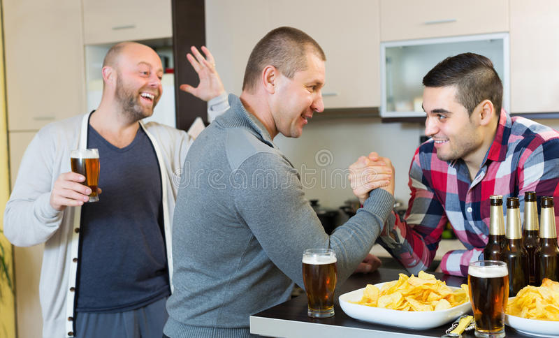 Friends armwrestling at the table. Two happy adult male friends armwrestling at the table with beer and chips royalty free stock images