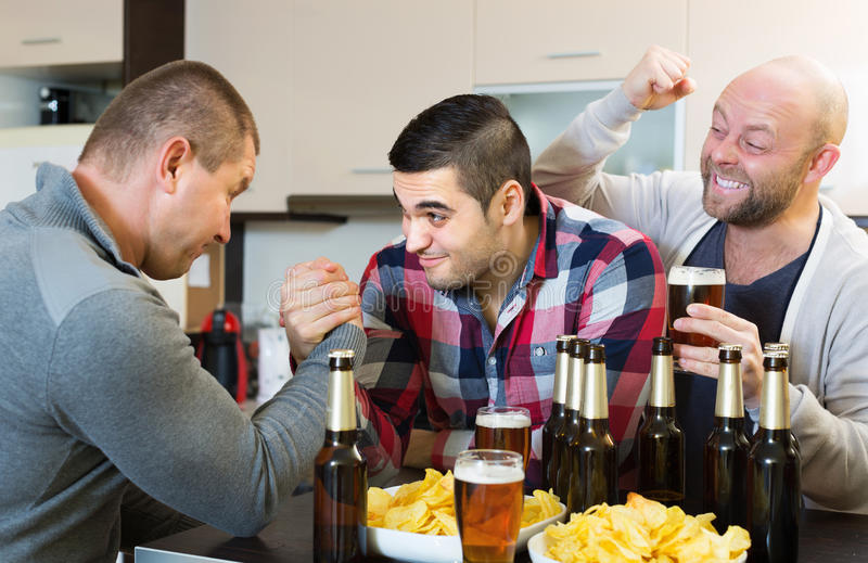 Friends armwrestling at the table. Two smiling adult male friends armwrestling at the table with beer and chips royalty free stock photos