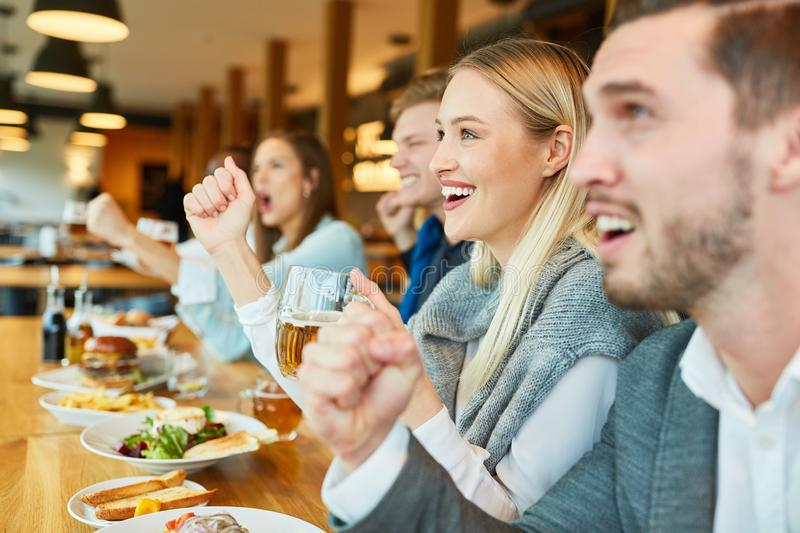 Sports fans at the bar of a bar look game royalty free stock photography