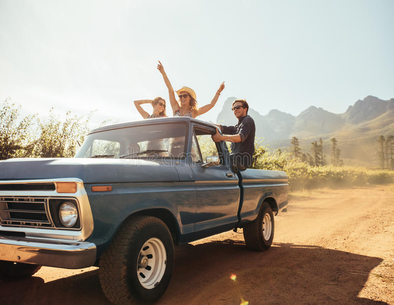 Friends at the back of a pick up truck having fun. Group of people at the back of a pick up truck having fun. Young men and women enjoying on a road trip in stock image