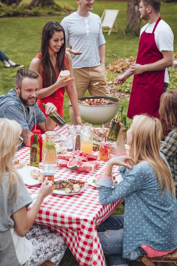 Friends in backyard enjoying meal. Group of friends in the backyard enjoying a meal, eating and drinking by a table and men in the back preparing more shashliks royalty free stock photography