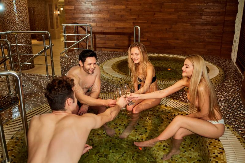 Friends in bathing suits with glass champagne rest in the bathro royalty free stock photography