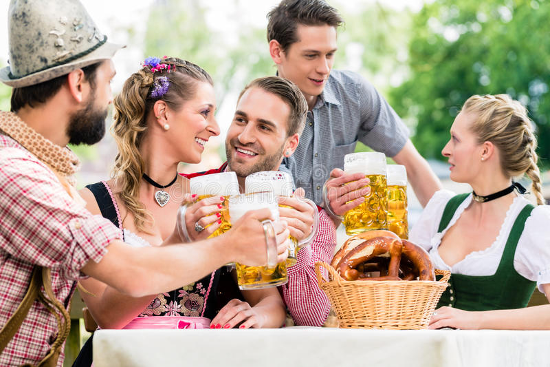 Friends in Bavarian beer garden drinking stock image