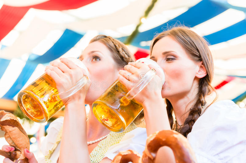 Friends in Bavarian beer tent drinking. Two friends drink beer from mugs at Bavarian folk fair in tent royalty free stock photography
