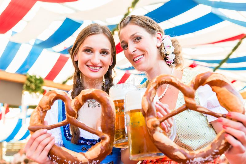 Friends at Bavarian Fair with giant pretzels. Two friends wearing dirndl are standing in a beer tent at Dult or Oktoberfest with giant pretzels stock image