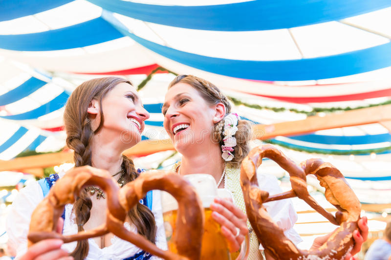 Friends at Bavarian Fair with giant pretzels. Two friends wearing dirndl are standing in a beer tent at Dult or Oktoberfest with giant pretzels stock images