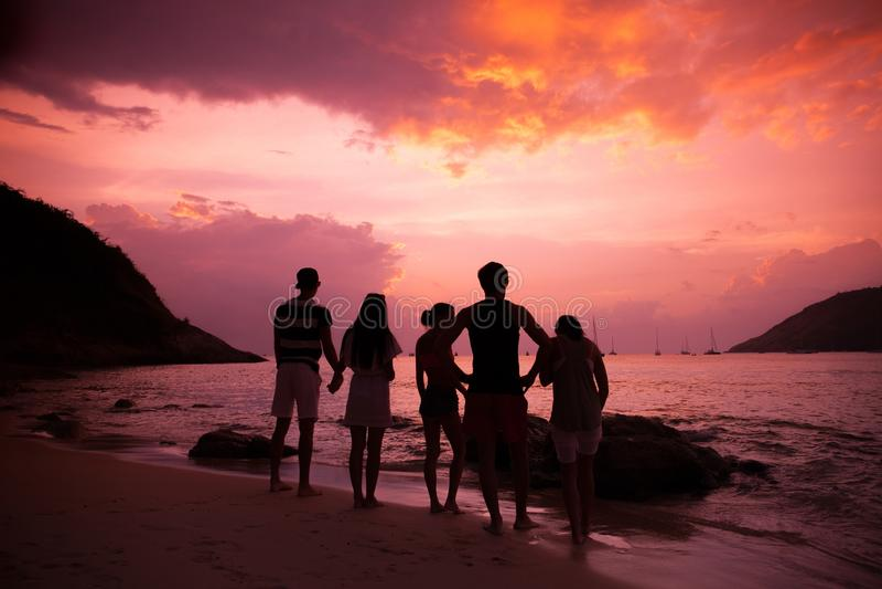 Friends on beach at sunset stock photos