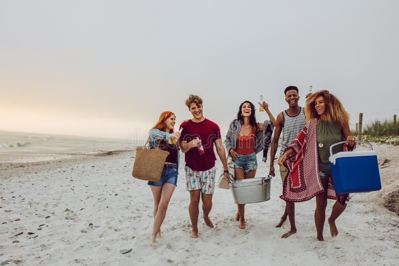 Friends on beach vacation. Group of young people walking on the beach carrying a cooler box and beverage tub. Young men and women on sea shore royalty free stock photography
