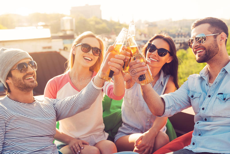 Friends and beer. Four young cheerful people cheering with beer and smiling while sitting at the bean bags on the roof of the building stock image