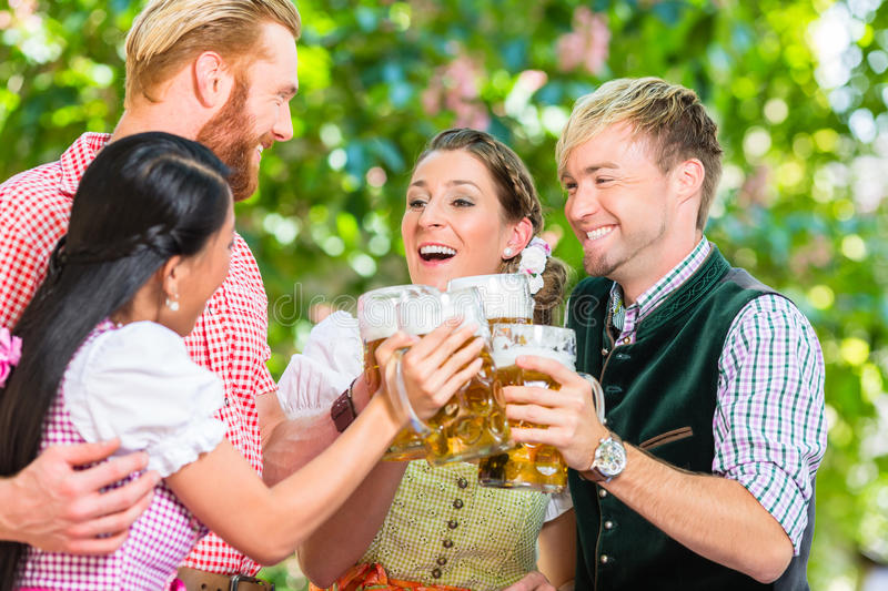 Friends in beer garden clinking glasses with beer royalty free stock photo