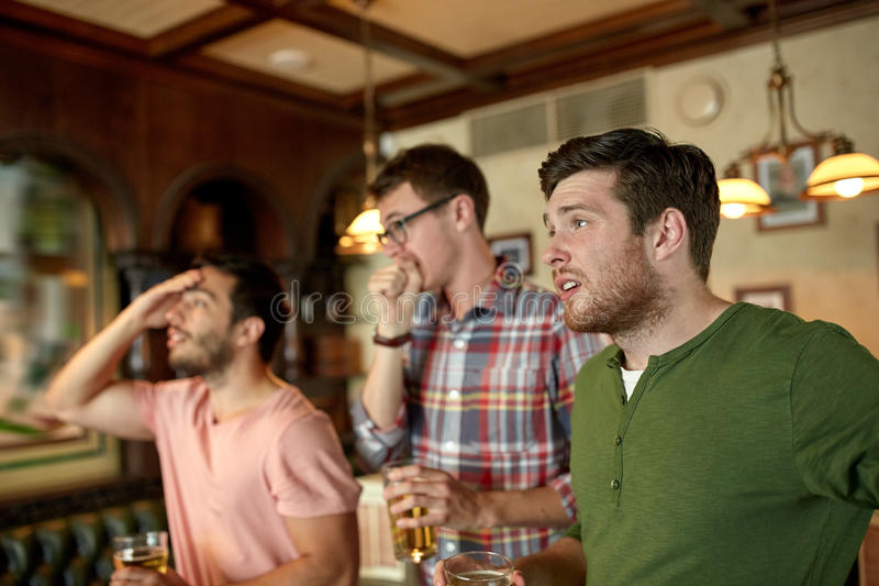 Friends with beer watching sport at bar or pub royalty free stock image