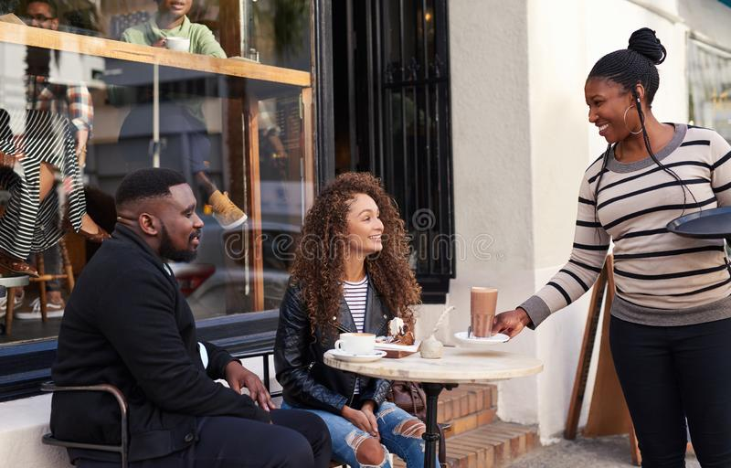 Friends being served by their waitress at a sidewalk cafe stock photo