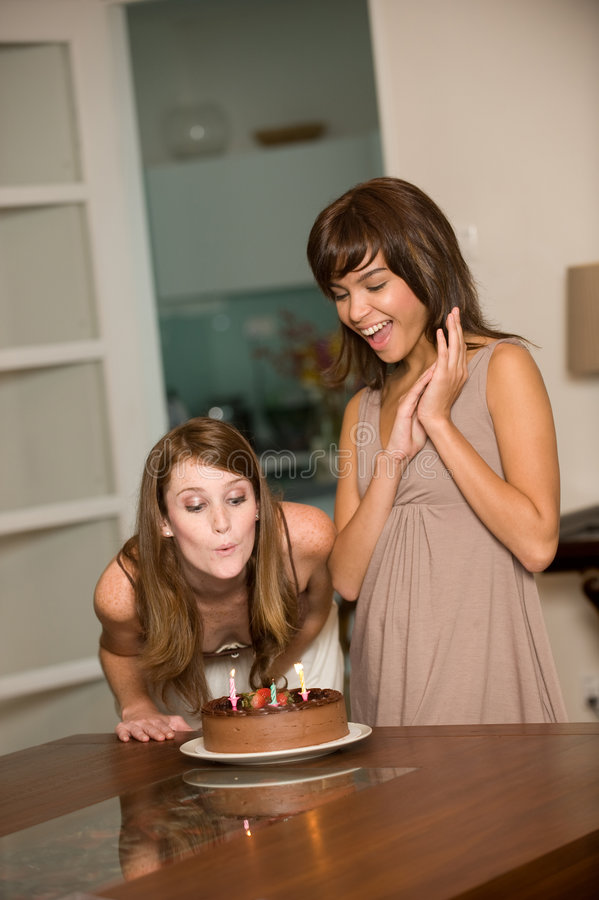 Friends With Birthday Cake. Two young attractive women celebrating a birthday with cake royalty free stock images
