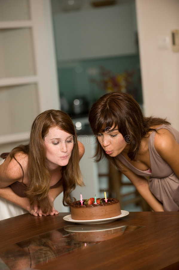 Friends With Birthday Cake. Two young attractive women celebrating a birthday with cake stock images