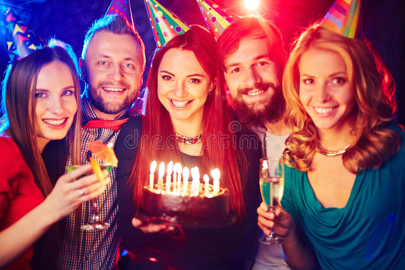 Friends with birthday cake. Joyful friends with birthday cake cheering in night club royalty free stock photography