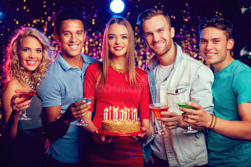 Friends on birthday party. Smiling friends with cocktails and cake with burning candles having birthday party stock image