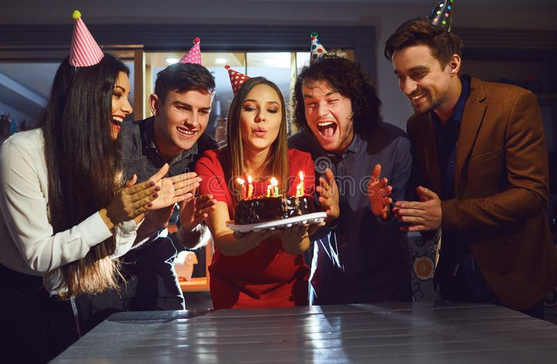 Friends blowing birthday candles on the cake indoors royalty free stock photos