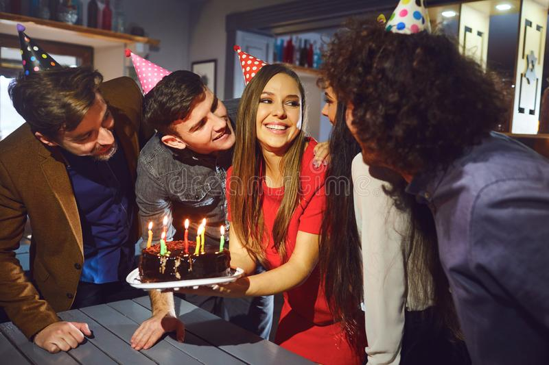 Friends blowing birthday candles on the cake indoors royalty free stock photography