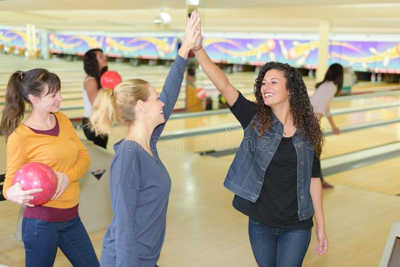 Friends bowling at club and having fun playing casually stock image
