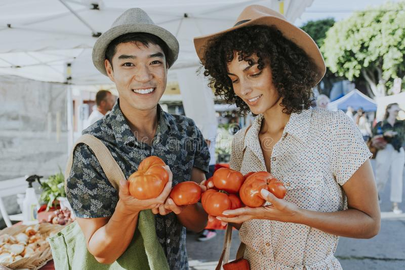 Friends buying fresh tomatoes at a farmers market royalty free stock photography