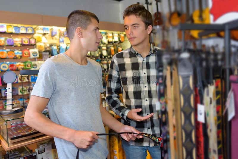 Friends buying guitar strap in guitar shop. Music royalty free stock images