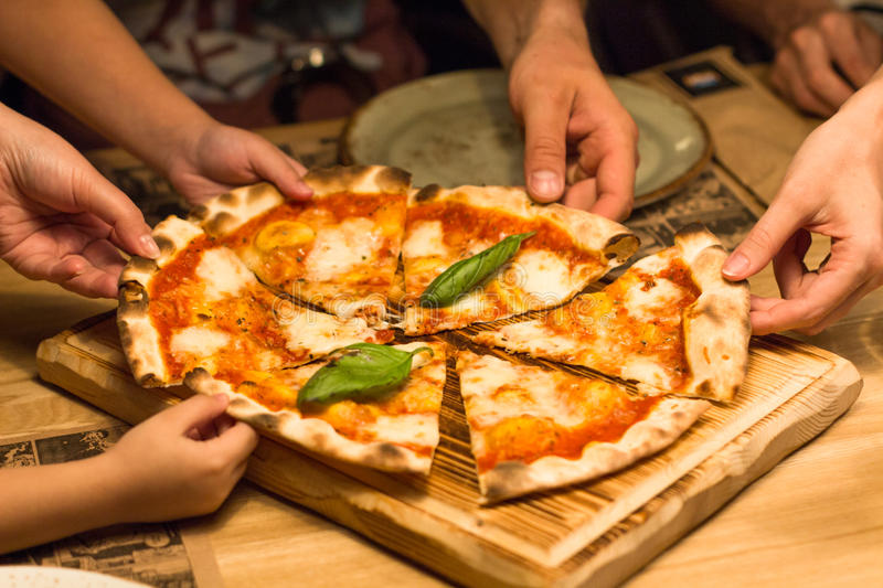 Friends in a cafe hands taking slices of pizza margherita royalty free stock photos