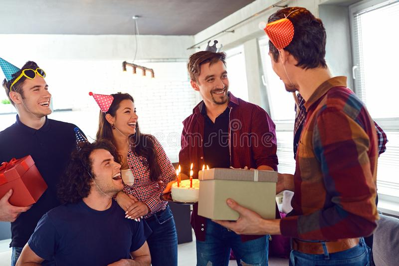 Friends with cake with candles celebrating birthday at a party. stock photo