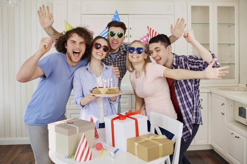 Friends with cake celebrating birthday at a party. royalty free stock photography