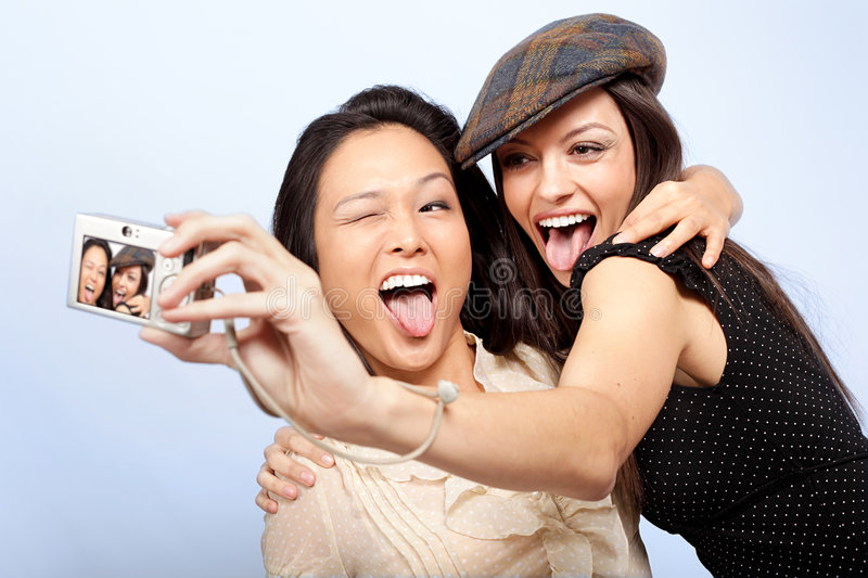 Friends with camera. Happy, hugging friends taking pictures on their digital camera royalty free stock photo