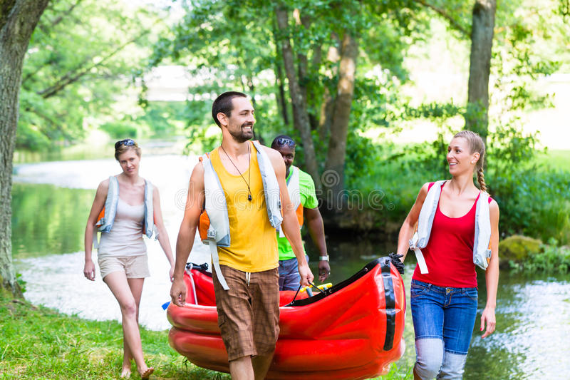 Friends carrying kayak or canoe to forest river stock photo