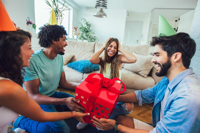 Friends celebrating birthday and giving gift to a girl. At home party royalty free stock images