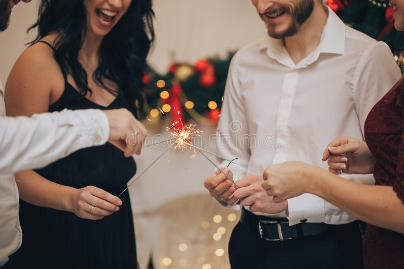 Friends celebrating Christmas or New Year eve party with Bengal lights royalty free stock photos