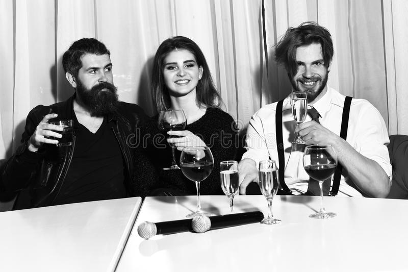 Friends celebrating at karaoke party. On white curtain. Two bearded men, hipsters with beards, holding microphones for pretty girl or beautiful women for stock image
