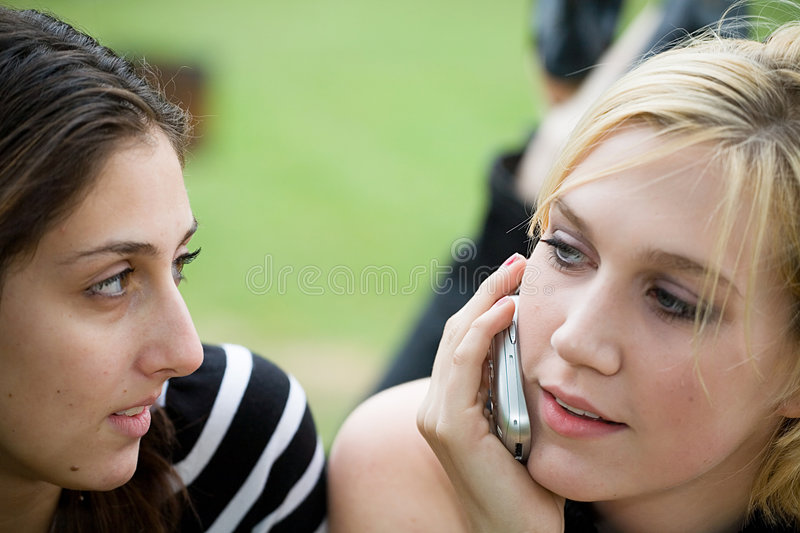 Friends on Cell Phone together (Beautiful Young Blonde and Brunette Girls) royalty free stock photos