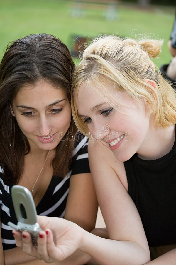 Friends on Cell Phone together (Beautiful Young Blonde and Brunette Girls) stock photography