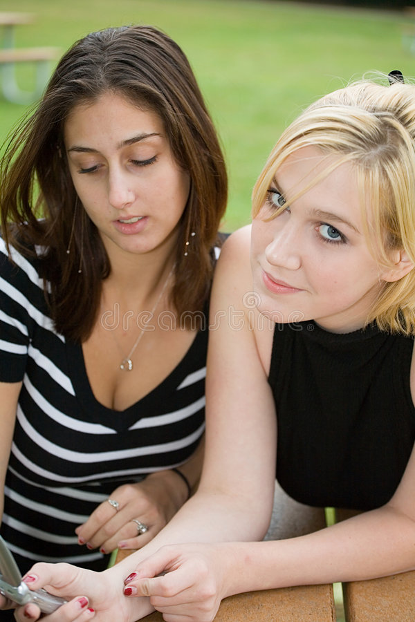 Friends on Cell Phone together (Beautiful Young Blonde and Brunette Girls) royalty free stock image