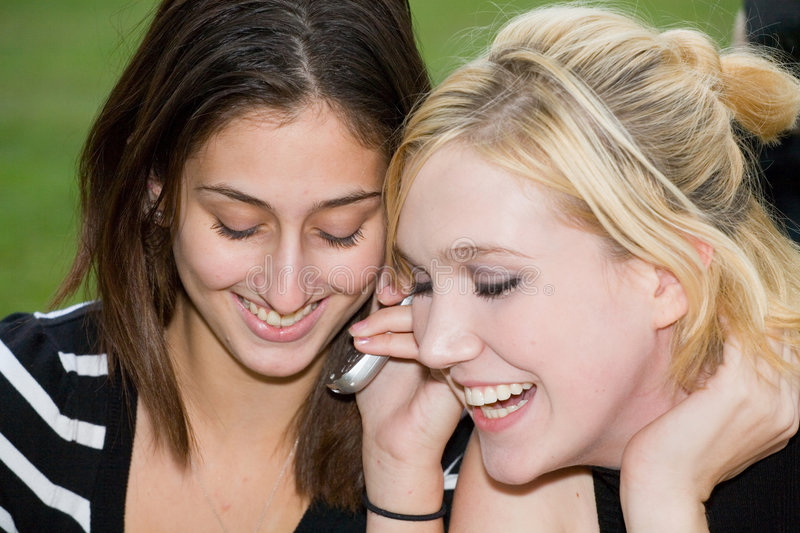 Friends on Cell Phone together (Beautiful Young Blonde and Brunette Girls) stock images