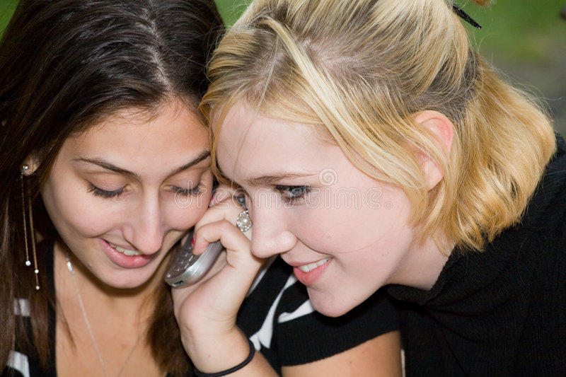 Friends on Cell Phone together (Beautiful Young Blonde and Brunette Girls) stock image