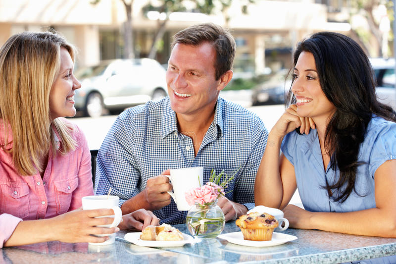 Friends chatting outside cafe. Smiling stock images