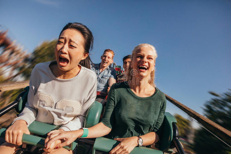 Friends cheering and riding roller coaster at amusement park stock images