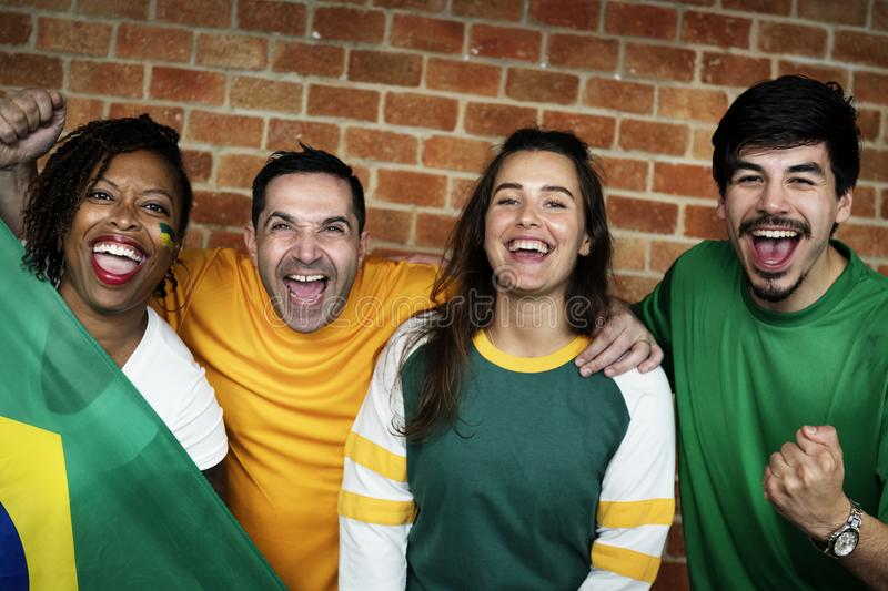 Friends cheering world cup with painted flag stock photography
